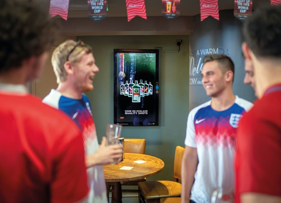 Football fans in a pub with a digital advertising screen