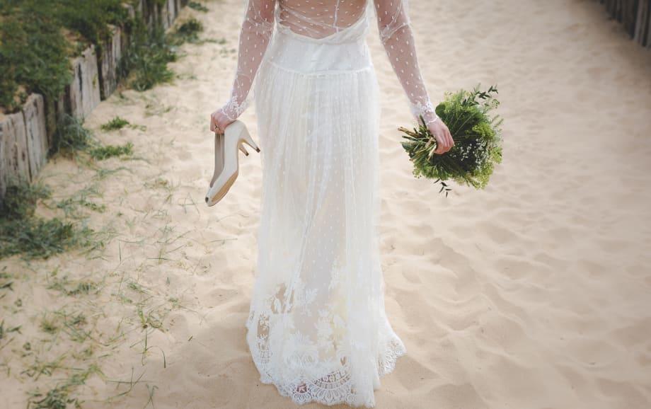 Bride walking on sand
