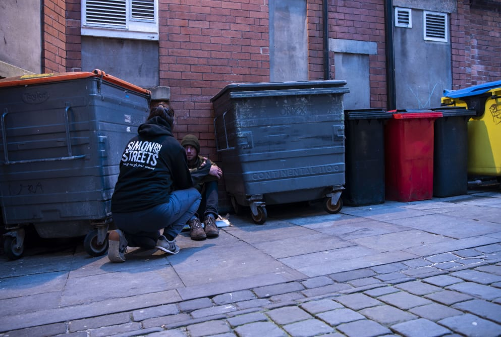 An outreach is bending down on one knee to talk to a man sat on the floor between two bins