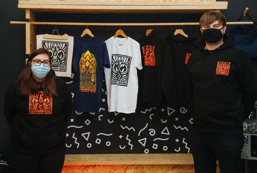 A man and women stand at either end of the photo. Both are wearing hoodies with the Keep Leeds Warm logo on. Keep Leeds Warm t-shirts are displayed behind them