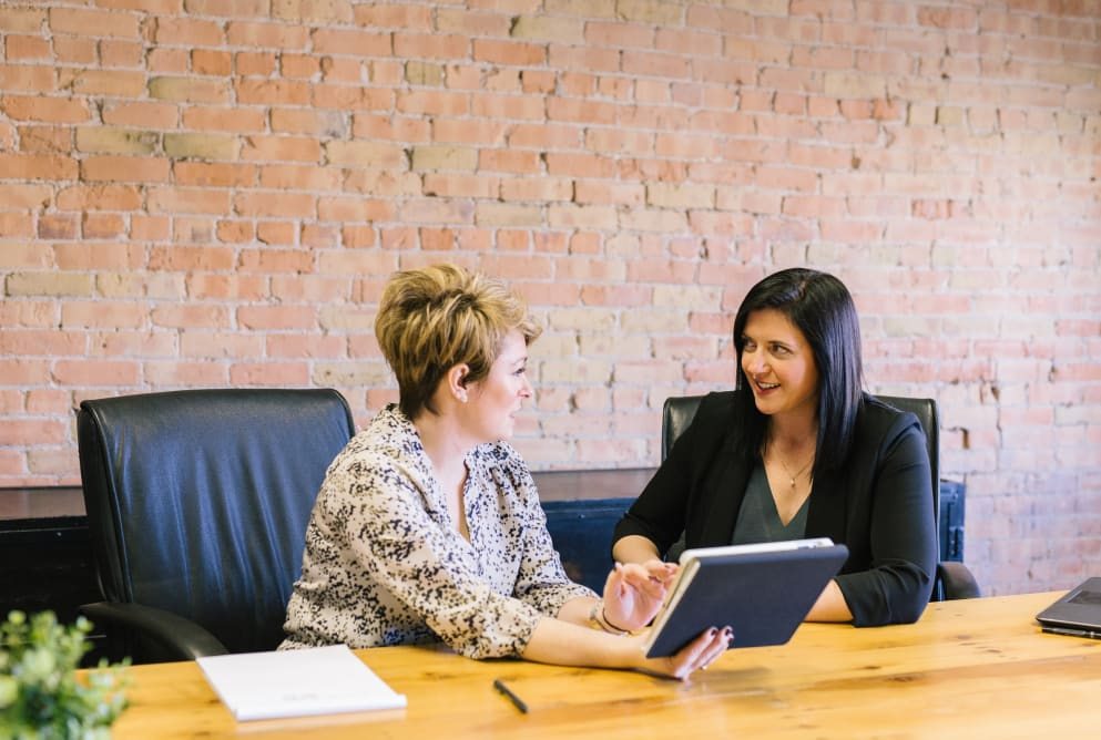 Two women talk at a desk. Mental wellbeing at work