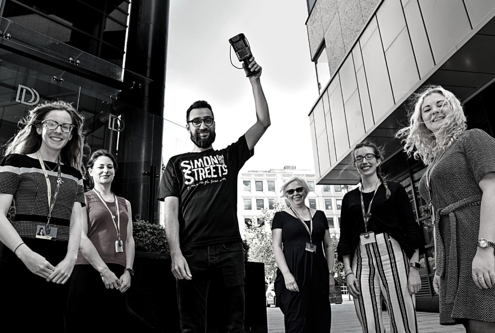 A group of people stand smiling at the camera. A man in the middle wears a Simon on the Streets t-shirt and holds up a collection tin.