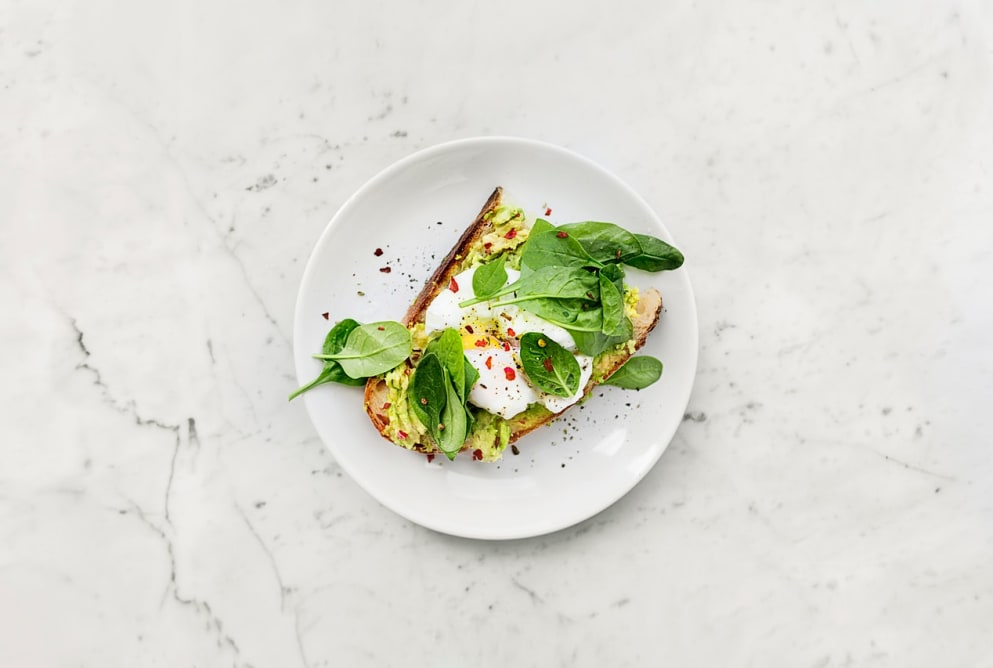 A plate of avocado toast on a marble counter