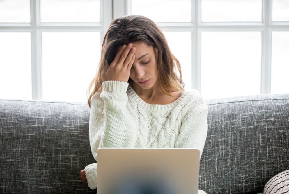 A woman puts her head to her forehead whilst staring at her laptop. She looks worried.