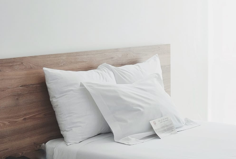 A clean bed in a hotel with white sheets