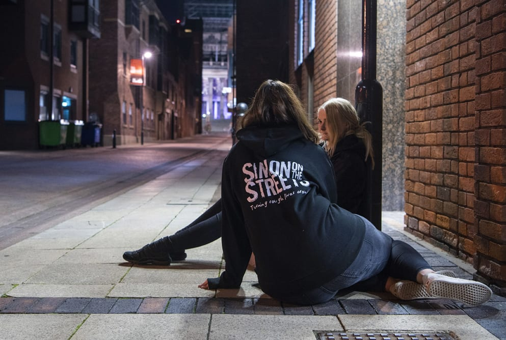 An outreach worker sits on the floor talking to a woman