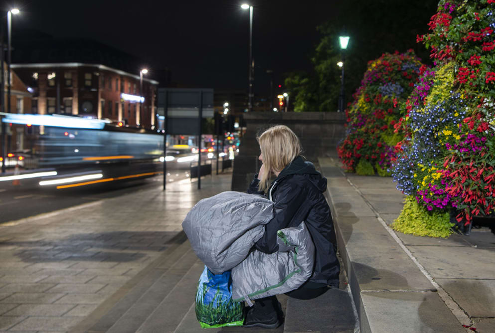 A woman sits on some steps. She has a sleeping bag in her lap. Cars speed off past her. Flowers can be seen behind her.