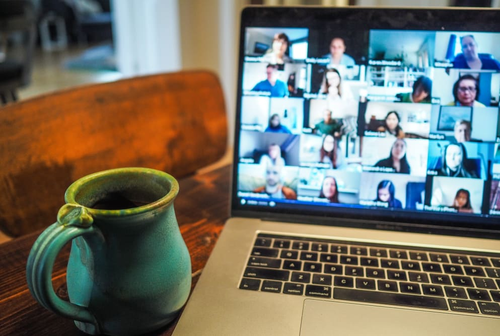 A laptop screen shows a virtual meeting on the screen with many participants. A cup sits on the side next to the laptop.