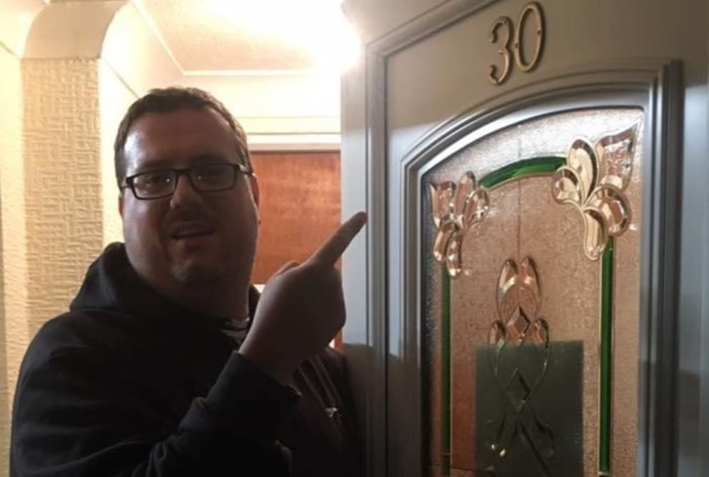A man named Ricky standing outside and pointing to a door with the number 30 on it