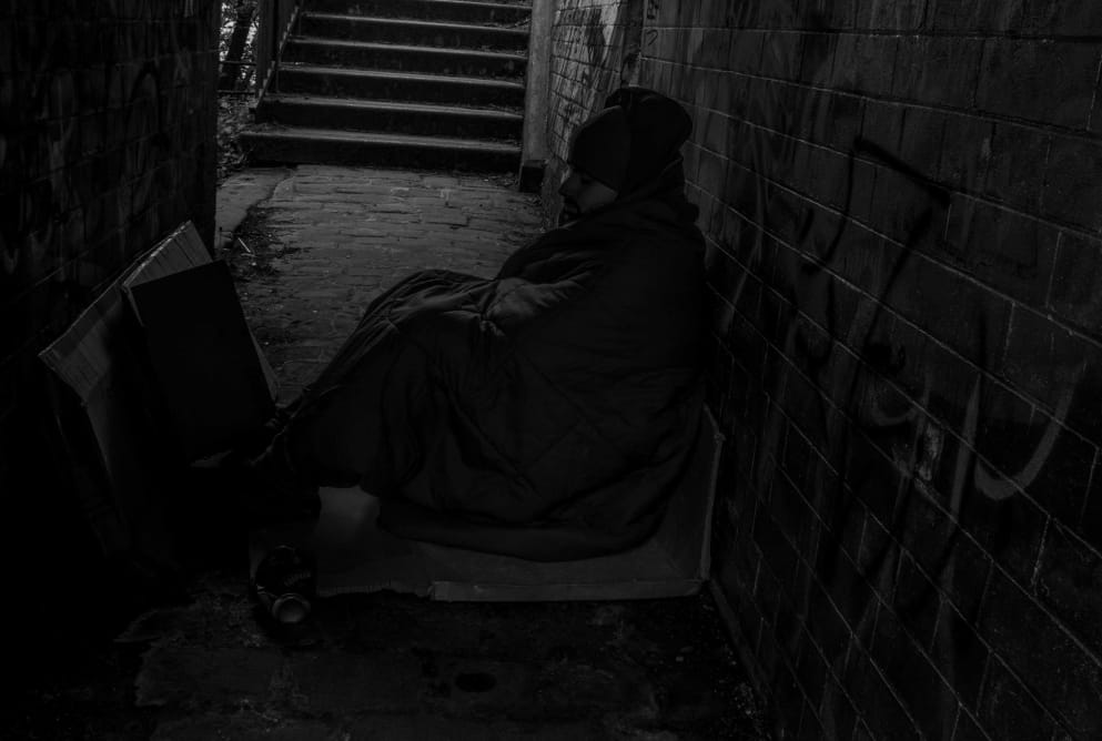 A man is sat on a piece of cardboard. He is in an alleyway. Graffiti covers the wall behind him.