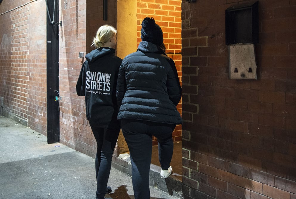 Two women walk through a doorway. The woman on the left has a Simon on the Streets hoodie on.