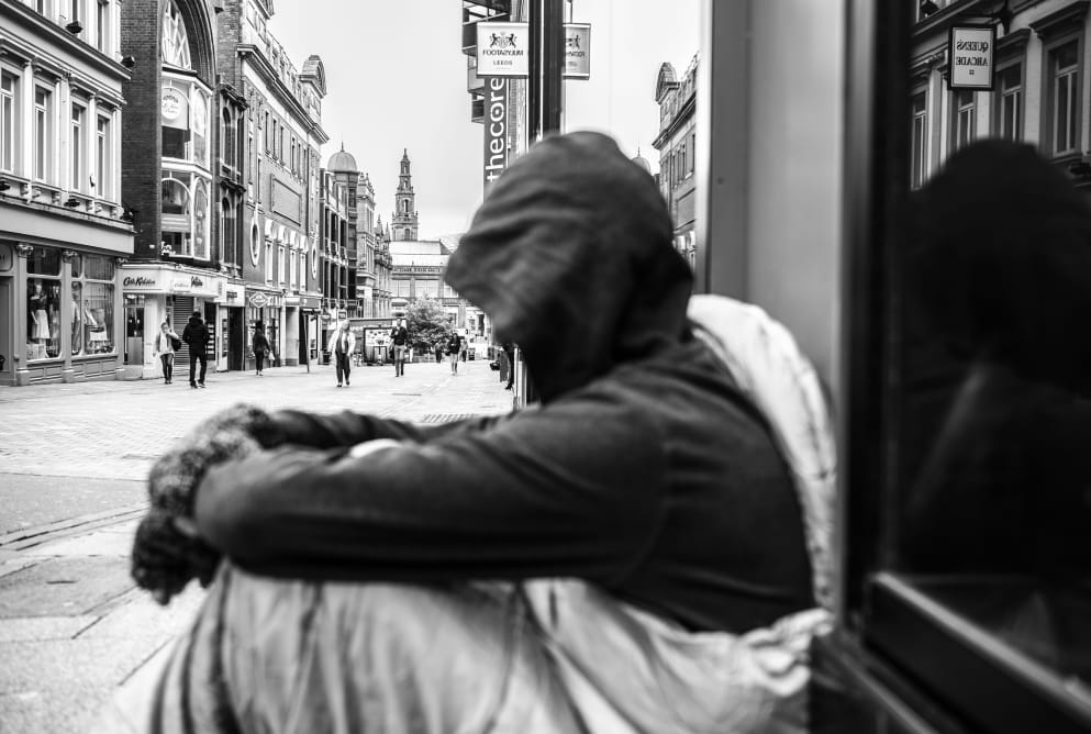 A man is sat on the ground with his hood up. He is in a sleeping bag. He gazes down the street, where buildings can be seen in the distance.