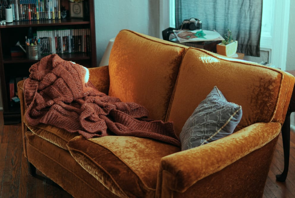 A red blanket and a grey cushion are on top of an orange sofa.