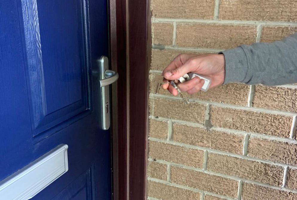 A man's hand holds keys to a blue door.