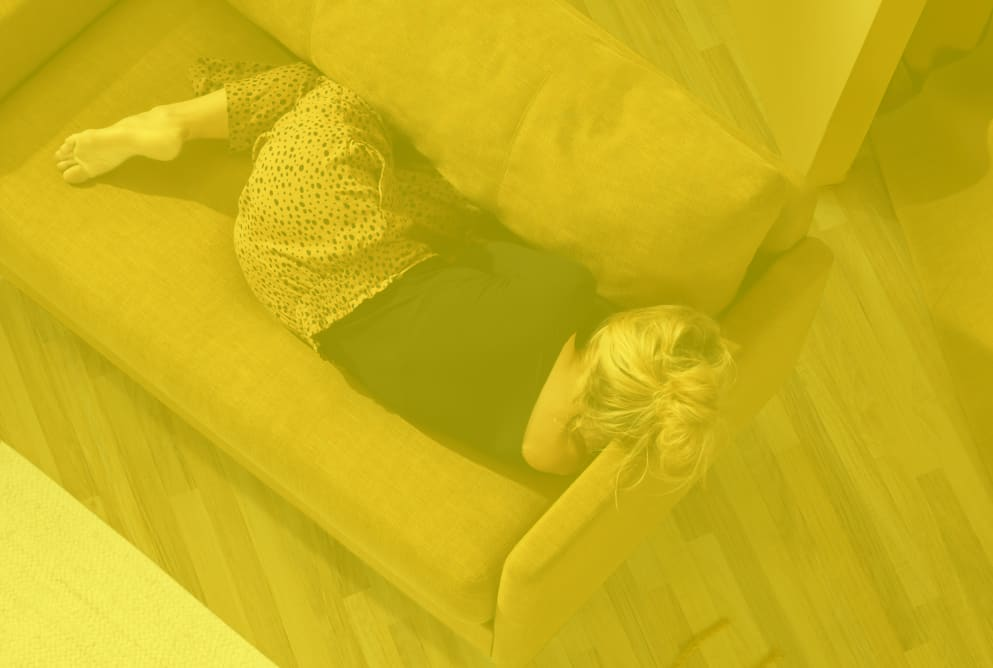 A woman is sleeping on a sofa with her back turned away from the camera. The photograph has a yellow tint.