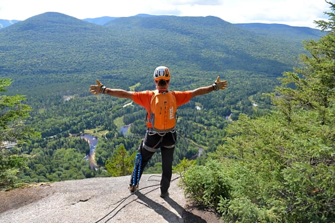 Homme avec sac à dos Petzl au sommet du parcours de la via ferrata du Parc national du Mont-Tremblant