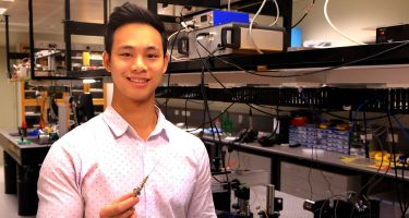 Anthony Phan holding a microscope-in-a-needle.