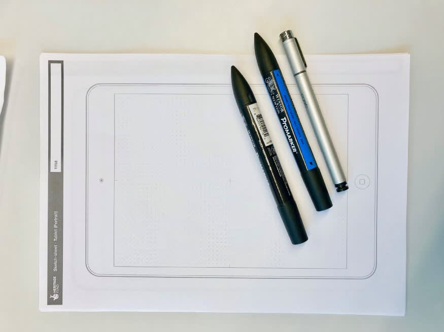 Photo from above of a sketch sheet and sketching pens