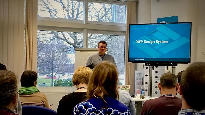 Paul, stood up presenting infront of a TV Screen with the title DWP Design System