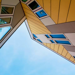 Looking up at yellow and white clad Cube Houses.