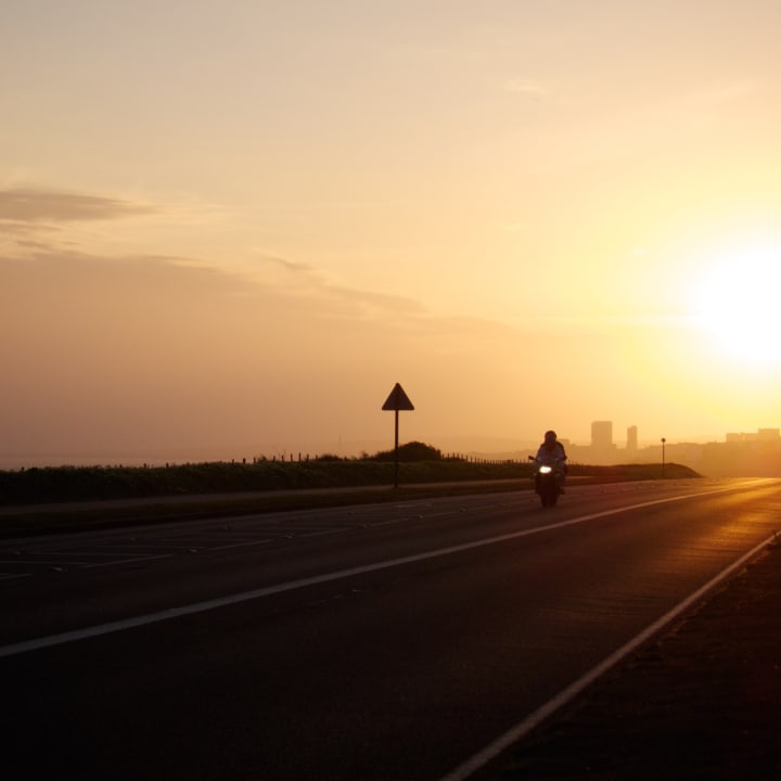 Motorbike on a road leaving Brighton at sunset