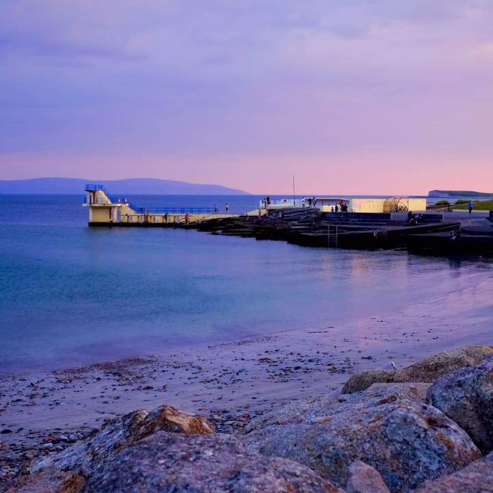 Dusk creates a pink light over the Blackrock Diving Tower in Salthill