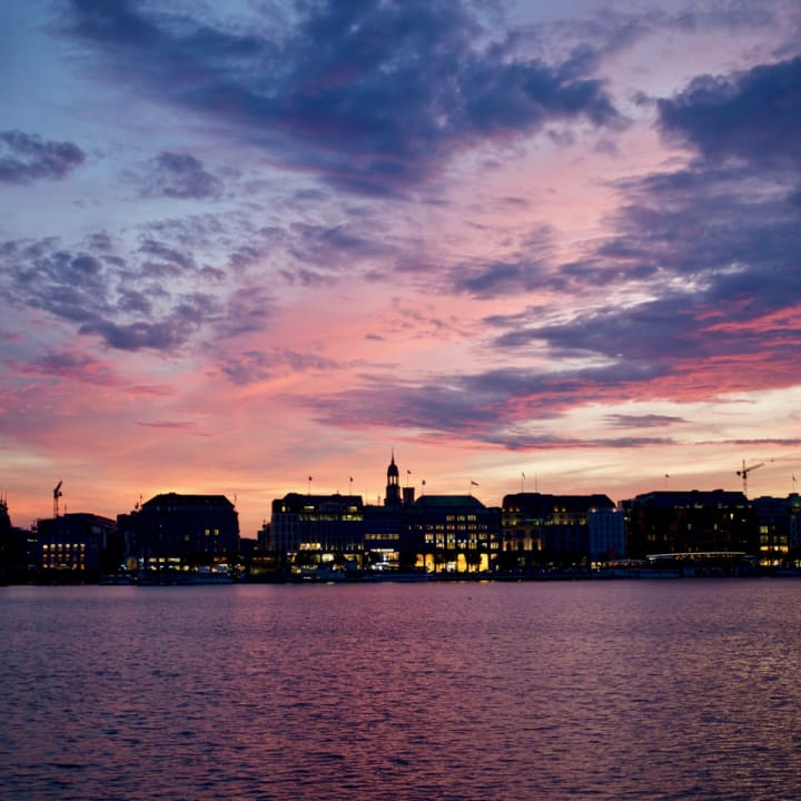 Vivid sunset over Binnenalster with cityscape in the distance