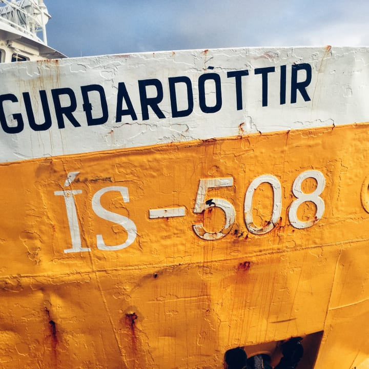 Yellow hull of a fishing boat with identification number ÍS-508