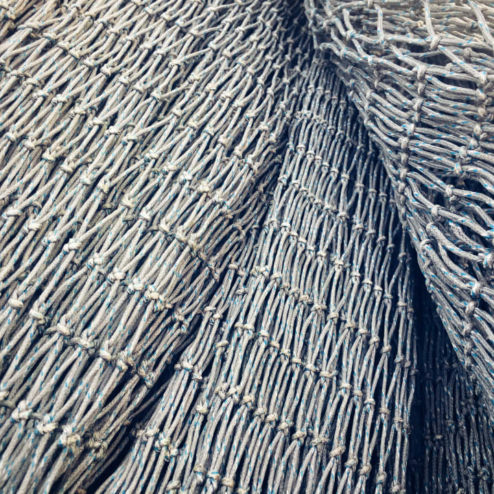 Closeup detail of stacked grey fish nets