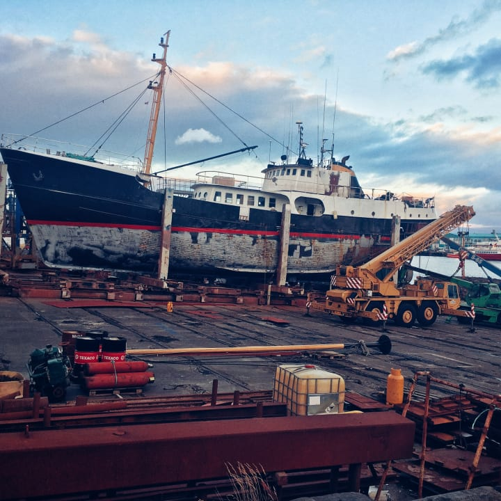 A boat in dry dock being repaired