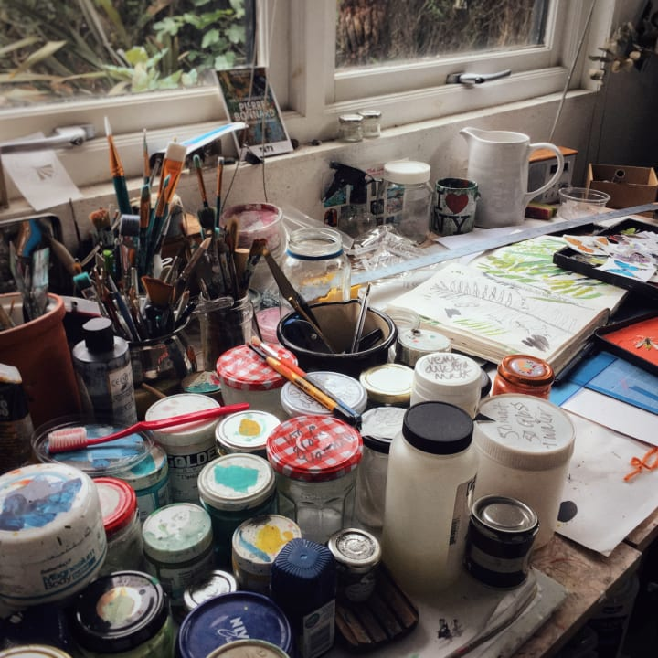 A desk covered with brushes, pots, sketches and other materials.