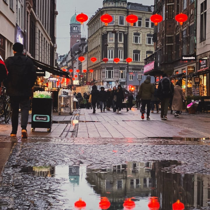 A pedrestrian street with puddles reflecting the red Chinese lantens hung overhead.