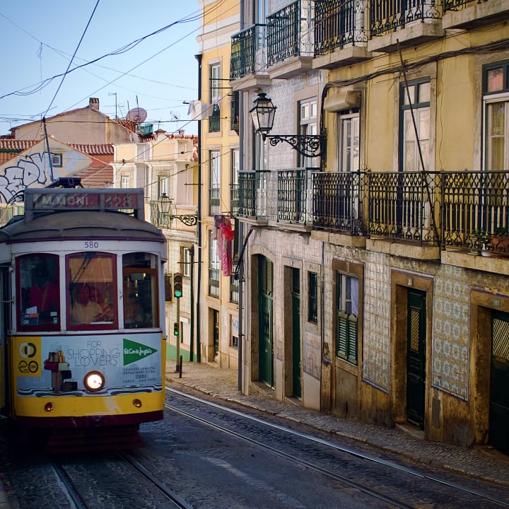 Tram travelling down a narrow street.