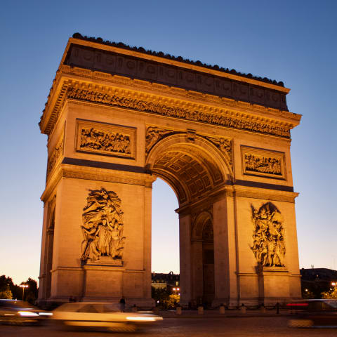An illuminated Arc de Triomphe as dusk falls.