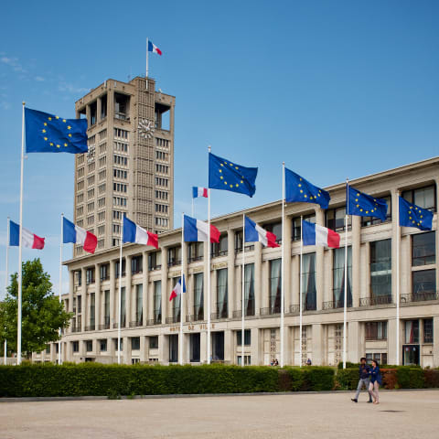 Modern building with French and EU flags flying outside.