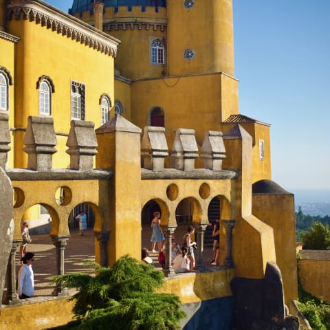 Yellow Romanticist castle sat behind a large turretted wall.