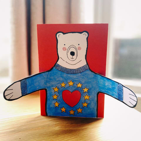 A homemade Christmas card. A polar bear wearing an EU flag jumper has his arms open offering a bear hug.