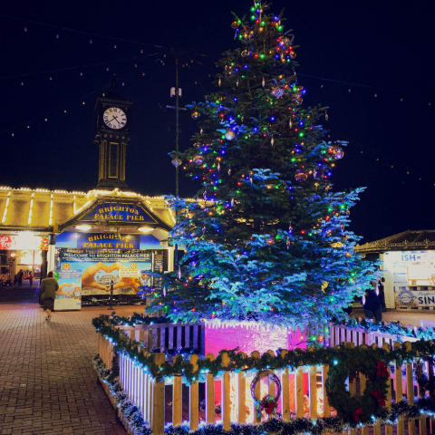 A Christmas tree decorated with lights in front of the entrance to the pier.