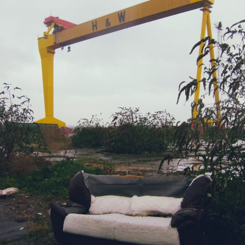 A disused sofa with a large yellow sat behind it.