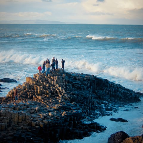 Several people stood above the Giant's Causeway, with small waves approaching it.