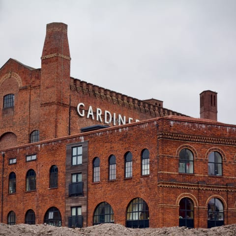 A refurbished red brick building with rubble in the foreground.