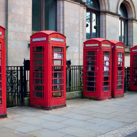 A row of 8 red K6 telephone boxes.