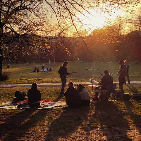 People playing musical instruments in Preston Park as the sun sets.