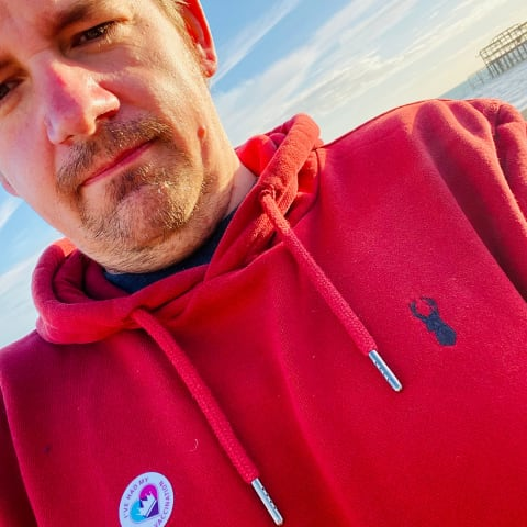 Photo of me on Brighton beach wearing a COVID-19 vaccination sticker.