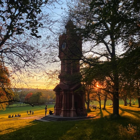 Clock tower in Preston Park with the sun setting behind it.
