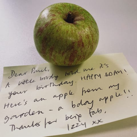 An apple sat atop a Post-it note with a birthday message.