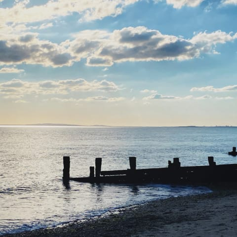 Beach groyne partly submerged in the sea as the sun sets behind it.