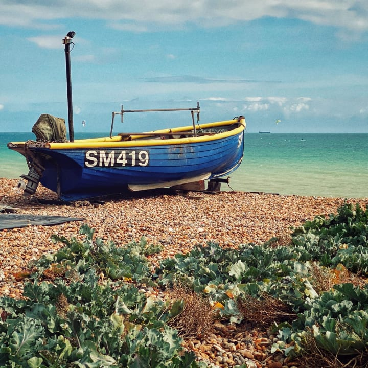 Small blue fishing boat on Worthing beach.