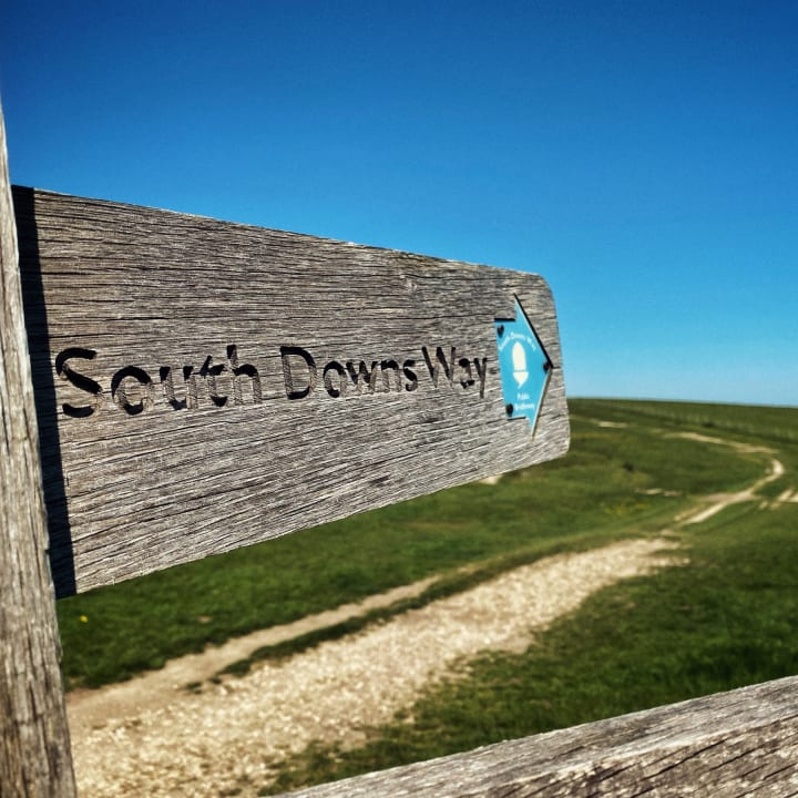 Signpost pointing east that says 'South Downs Way'.