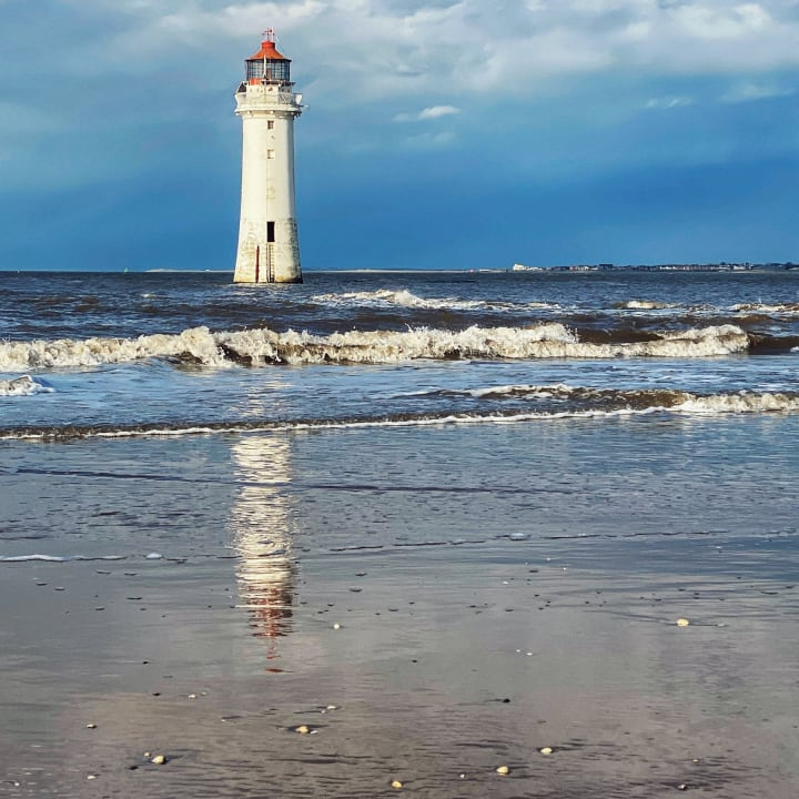 Perch Rock Lighthouse reflected on the wet beach.